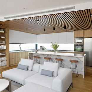 Свежая идея для дизайна: большая угловая кухня-гостиная в современном стиле с врезной раковиной, плоскими фасадами, светлыми деревянными фасадами, мраморной столешницей, фартуком с окном, черной техникой, светлым паркетным полом, островом, коричневым полом, белой столешницей и потолком из вагонки - отличное фото интерьера