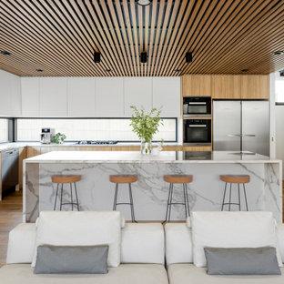 Пример оригинального дизайна: большая угловая кухня-гостиная в современном стиле с врезной раковиной, плоскими фасадами, светлыми деревянными фасадами, мраморной столешницей, фартуком с окном, черной техникой, светлым паркетным полом, островом, коричневым полом, белой столешницей и потолком из вагонки