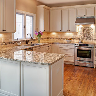 Small traditional eat-in kitchen designs - Small elegant u-shaped medium tone wood floor eat-in kitchen photo in Charlotte with a single-bowl sink, flat-panel cabinets, white cabinets, granite countertops, beige backsplash, stone tile backsplash, stainless steel appliances and a peninsula
