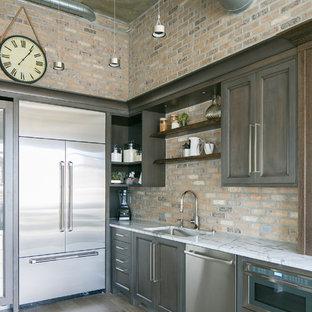 デンバーの中くらいのインダストリアルスタイルのおしゃれなキッチン (アンダーカウンターシンク、シェーカースタイル扉のキャビネット、中間色木目調キャビネット、クオーツストーンカウンター、レンガのキッチンパネル、シルバーの調理設備、無垢フローリング、アイランドなし、グレーの床) の写真