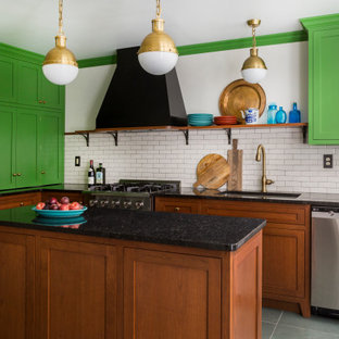 This is an example of a mid-sized eclectic l-shaped eat-in kitchen in Philadelphia with an undermount sink, shaker cabinets, green cabinets, granite benchtops, white splashback, ceramic splashback, stainless steel appliances, slate floors, with island, green floor and black benchtop.