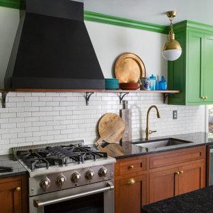 Неиссякаемый источник вдохновения для домашнего уюта: угловая кухня среднего размера в стиле фьюжн с обеденным столом, врезной раковиной, фасадами в стиле шейкер, зелеными фасадами, гранитной столешницей, белым фартуком, фартуком из керамической плитки, техникой из нержавеющей стали, полом из сланца, островом, зеленым полом и черной столешницей