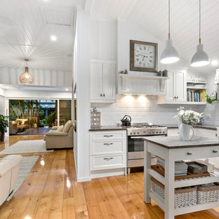 Photo of a small beach style u-shaped open plan kitchen in Brisbane with a farmhouse sink, white cabinets, granite benchtops, white splashback, ceramic splashback, stainless steel appliances, with island, recessed-panel cabinets, medium hardwood floors, brown floor and grey benchtop.