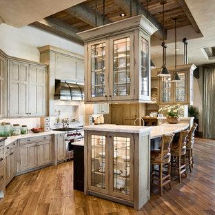 Aménagement d'une cuisine américaine montagne avec un placard à porte vitrée, des portes de placard beiges, une crédence beige et un électroménager en acier inoxydable.