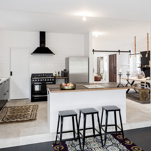 This is an example of a mid-sized scandinavian galley open plan kitchen in Sydney with a double-bowl sink, black cabinets, wood benchtops, white splashback, subway tile splashback, black appliances, limestone floors and with island.