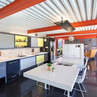 Ejemplo de cocina vintage, abierta, con fregadero encastrado, armarios con paneles lisos, puertas de armario amarillas, electrodomésticos con paneles, una isla, suelo negro y encimeras blancas