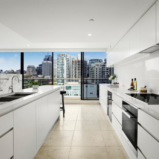 Inspiration for a contemporary galley kitchen in Sydney with an undermount sink, flat-panel cabinets, white cabinets, white splashback, black appliances, with island, beige floor and white benchtop.