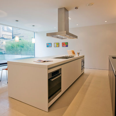 Mid-sized minimalist single-wall eat-in kitchen photo in London with flat-panel cabinets, black cabinets, stainless steel appliances and an island