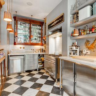 ロンドンの中くらいのエクレクティックスタイルのおしゃれなコの字型キッチン (ガラス扉のキャビネット、濃色木目調キャビネット、白いキッチンパネル、シルバーの調理設備、塗装フローリング、アイランドなし、マルチカラーの床) の写真
