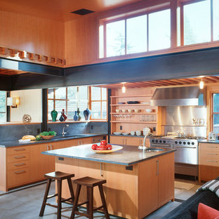 Contemporary kitchen designs - Example of a trendy u-shaped concrete floor and gray floor kitchen design in Seattle with an undermount sink, flat-panel cabinets, medium tone wood cabinets, gray backsplash, stainless steel appliances, an island and gray countertops