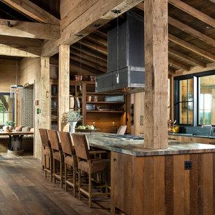Inredning av ett rustikt stort grå grått kök, med en undermonterad diskho, släta luckor, granitbänkskiva, svart stänkskydd, stänkskydd i sten, integrerade vitvaror, en köksö, brunt golv, skåp i mellenmörkt trä och mörkt trägolv