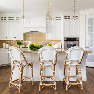 Große Maritime Küche in U-Form mit Landhausspüle, profilierten Schrankfronten, Küchengeräten aus Edelstahl, braunem Holzboden, Kücheninsel, braunem Boden, weißen Schränken, Küchenrückwand in Orange, Rückwand aus Metrofliesen und beiger Arbeitsplatte in Sonstige