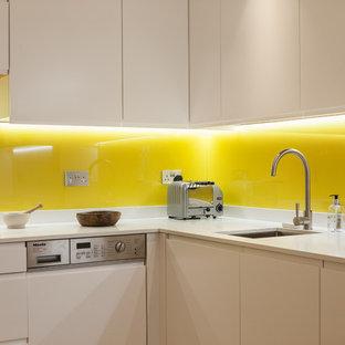 ロンドンの中サイズのエクレクティックスタイルのおしゃれなキッチン (アンダーカウンターシンク、フラットパネル扉のキャビネット、白いキャビネット、珪岩カウンター、黄色いキッチンパネル、ガラス板のキッチンパネル、シルバーの調理設備の、淡色無垢フローリング、アイランドなし) の写真