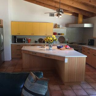 フェニックスの中サイズのエクレクティックスタイルのおしゃれなキッチン (アンダーカウンターシンク、フラットパネル扉のキャビネット、黄色いキャビネット、クオーツストーンカウンター、グレーのキッチンパネル、ボーダータイルのキッチンパネル、シルバーの調理設備、トラバーチンの床、茶色い床) の写真