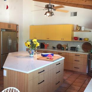 フェニックスの中サイズのエクレクティックスタイルのおしゃれなキッチン (アンダーカウンターシンク、フラットパネル扉のキャビネット、黄色いキャビネット、クオーツストーンカウンター、グレーのキッチンパネル、ボーダータイルのキッチンパネル、シルバーの調理設備の、トラバーチンの床、茶色い床) の写真