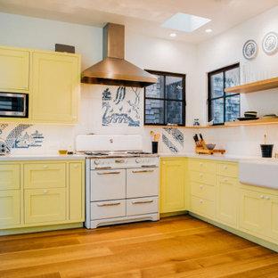 サンフランシスコの広いエクレクティックスタイルのおしゃれなキッチン (エプロンフロントシンク、シェーカースタイル扉のキャビネット、黄色いキャビネット、白いキッチンパネル、磁器タイルのキッチンパネル、白い調理設備、無垢フローリング、アイランドなし、茶色い床、白いキッチンカウンター) の写真