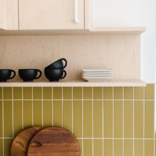 Small scandinavian l-shaped separate kitchen in Los Angeles with beige cabinets, yellow splashback, ceramic splashback, white appliances, concrete floors, no island, multi-coloured floor and white benchtop.