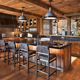 Свежая идея для дизайна: большая угловая кухня в стиле рустика с раковиной в стиле кантри, фасадами цвета дерева среднего тона, столешницей из известняка, фартуком из известняка, техникой из нержавеющей стали, паркетным полом среднего тона, островом, коричневым полом, фасадами в стиле шейкер, черным фартуком и черной столешницей - отличное фото интерьера