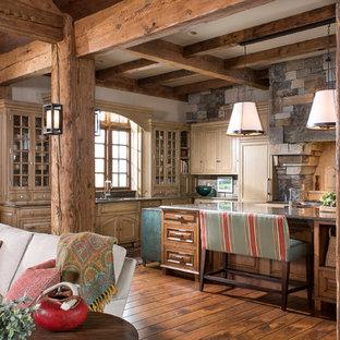 Ejemplo de cocina en L, rural, abierta, con armarios tipo vitrina, puertas de armario de madera clara, suelo de madera en tonos medios, una isla y suelo naranja