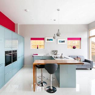 サセックスの大きいコンテンポラリースタイルのおしゃれなキッチン (フラットパネル扉のキャビネット、青いキャビネット、ドロップインシンク、木材カウンター、白いキッチンパネル、パネルと同色の調理設備、セラミックタイルの床) の写真