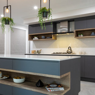 Photo of a contemporary galley kitchen in Other with flat-panel cabinets, grey cabinets, white splashback, a peninsula, grey floor and white benchtop.