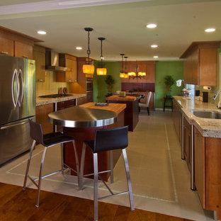 オレンジカウンティの中くらいのアジアンスタイルのおしゃれなダイニングキッチン (シングルシンク、フラットパネル扉のキャビネット、中間色木目調キャビネット、珪岩カウンター、緑のキッチンパネル、ガラスタイルのキッチンパネル、シルバーの調理設備、磁器タイルの床) の写真