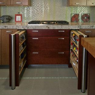 オレンジカウンティの中サイズのアジアンスタイルのおしゃれなキッチン (シングルシンク、フラットパネル扉のキャビネット、濃色木目調キャビネット、珪岩カウンター、緑のキッチンパネル、ガラスタイルのキッチンパネル、シルバーの調理設備の、磁器タイルの床) の写真