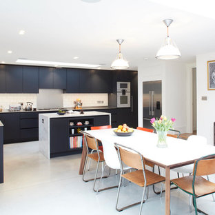 Inspiration for a large contemporary l-shaped open plan kitchen in London with a double-bowl sink, flat-panel cabinets, blue cabinets, stainless steel worktops, white splashback, metro tiled splashback, integrated appliances, an island, grey floors and white worktops.