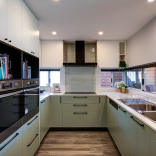 Inspiration for a contemporary u-shaped kitchen in Perth with white benchtop, a double-bowl sink, flat-panel cabinets, green cabinets, stainless steel appliances and brown floor.