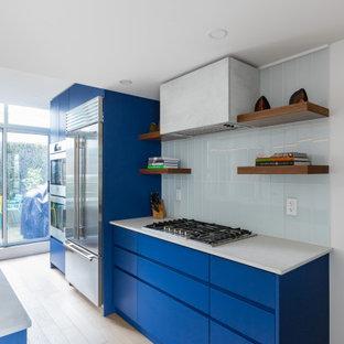 バンクーバーの広いモダンスタイルのおしゃれなキッチン (アンダーカウンターシンク、フラットパネル扉のキャビネット、青いキャビネット、珪岩カウンター、青いキッチンパネル、サブウェイタイルのキッチンパネル、シルバーの調理設備、クッションフロア、ベージュの床、白いキッチンカウンター) の写真