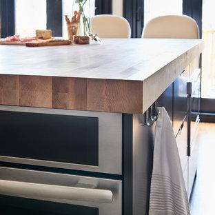 大きいモダンスタイルのおしゃれなキッチン (一体型シンク、フラットパネル扉のキャビネット、黒いキャビネット、木材カウンター、グレーのキッチンパネル、大理石のキッチンパネル、シルバーの調理設備、無垢フローリング、茶色い床) の写真
