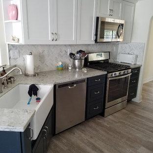 Inredning av ett lantligt stort grå grått kök, med en rustik diskho, luckor med upphöjd panel, blå skåp, granitbänkskiva, vitt stänkskydd, stänkskydd i stenkakel, rostfria vitvaror, laminatgolv och brunt golv