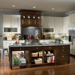 Mittelgroße Klassische Küche in L-Form mit Einbauwaschbecken, Lamellenschränken, weißen Schränken, Küchengeräten aus Edelstahl, braunem Holzboden, Kücheninsel und braunem Boden in Sonstige