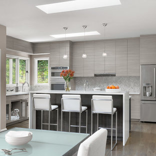 Contemporary eat-in kitchen designs - Example of a trendy l-shaped medium tone wood floor and brown floor eat-in kitchen design in St Louis with flat-panel cabinets, gray cabinets, gray backsplash, stainless steel appliances, an island and white countertops