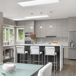 Idéer för att renovera ett mellanstort funkis vit vitt kök, med släta luckor, grå skåp, grått stänkskydd, rostfria vitvaror, mellanmörkt trägolv, en köksö, brunt golv, bänkskiva i kvarts och stänkskydd i porslinskakel