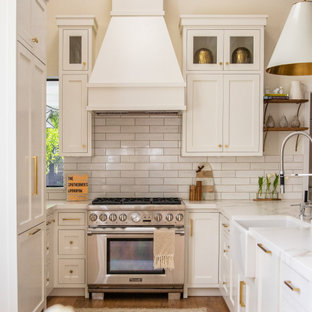 Farmhouse kitchen remodeling - Farmhouse u-shaped medium tone wood floor and brown floor kitchen photo in San Francisco with a farmhouse sink, shaker cabinets, white cabinets, white backsplash, stainless steel appliances, a peninsula and white countertops