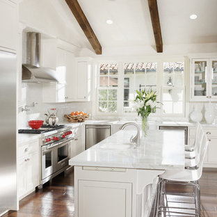 Example of a tuscan l-shaped kitchen design in San Francisco with shaker cabinets, white cabinets, white backsplash and stainless steel appliances