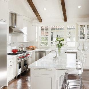 Esempio di una cucina a L mediterranea con ante in stile shaker, ante bianche, paraspruzzi bianco e elettrodomestici in acciaio inossidabile