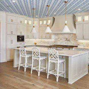 Cette photo montre une grand cuisine chic en L avec un évier encastré, un placard avec porte à panneau encastré, des portes de placard blanches, un plan de travail en marbre, une crédence en marbre, un sol en bois clair, un îlot central, une crédence grise, un électroménager encastrable, un sol beige, un plan de travail gris et un plafond en papier peint.
