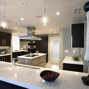 Ispirazione per una grande cucina ad U moderna chiusa con lavello a doppia vasca, ante lisce, ante nere, elettrodomestici in acciaio inossidabile, pavimento con piastrelle in ceramica e isola