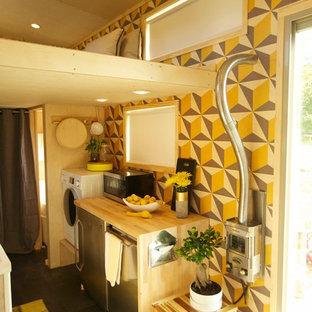 他の地域の小さいコンテンポラリースタイルのおしゃれなII型キッチン (フラットパネル扉のキャビネット、中間色木目調キャビネット、木材カウンター、シルバーの調理設備、クッションフロア) の写真