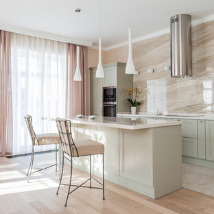 This is an example of a transitional single-wall kitchen in Other with recessed-panel cabinets, green cabinets, beige splashback, stainless steel appliances, with island, beige floor and white benchtop.