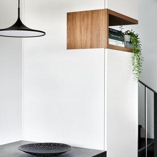 Immagine di una cucina moderna di medie dimensioni con lavello sottopiano, ante lisce, ante in legno scuro, top in vetro, paraspruzzi grigio, paraspruzzi in lastra di pietra, elettrodomestici neri, penisola e top grigio