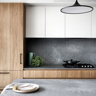 This is an example of a mid-sized contemporary galley eat-in kitchen in Sydney with an undermount sink, flat-panel cabinets, medium wood cabinets, glass benchtops, grey splashback, stone slab splashback, black appliances, a peninsula and grey benchtop.