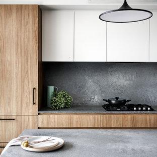 Bild på ett mellanstort funkis grå grått kök, med en undermonterad diskho, släta luckor, skåp i mellenmörkt trä, bänkskiva i glas, grått stänkskydd, stänkskydd i sten, svarta vitvaror och en halv köksö