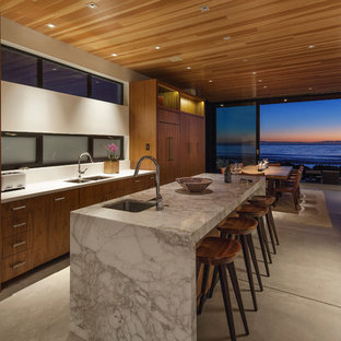Large contemporary eat-in kitchen inspiration - Inspiration for a large contemporary single-wall concrete floor eat-in kitchen remodel in Los Angeles with an undermount sink, flat-panel cabinets, medium tone wood cabinets, marble countertops, white backsplash, stainless steel appliances and an island