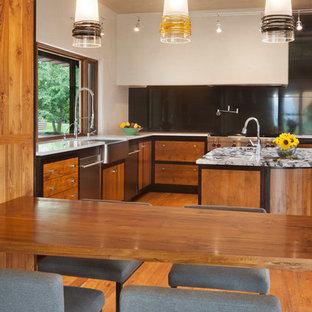 デンバーの大きいアジアンスタイルのおしゃれなキッチン (エプロンフロントシンク、フラットパネル扉のキャビネット、中間色木目調キャビネット、大理石カウンター、黒いキッチンパネル、大理石の床、シルバーの調理設備の、無垢フローリング、茶色い床) の写真