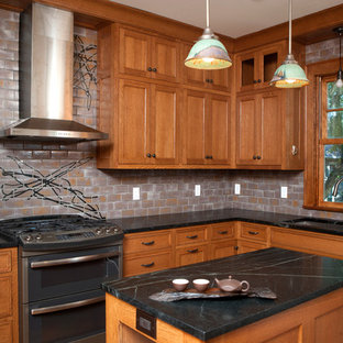 Design ideas for a mid-sized asian l-shaped separate kitchen in Minneapolis with an undermount sink, raised-panel cabinets, medium wood cabinets, soapstone benchtops, grey splashback, ceramic splashback, stainless steel appliances and with island.