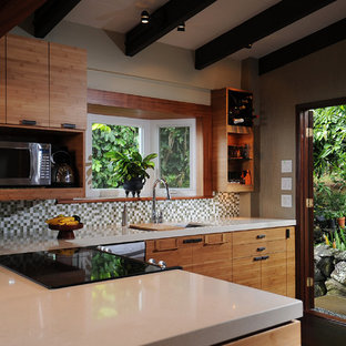 Mid-sized tropical eat-in kitchen remodeling - Example of a mid-sized island style u-shaped eat-in kitchen design in Hawaii with an undermount sink, flat-panel cabinets, medium tone wood cabinets, quartzite countertops, green backsplash, mosaic tile backsplash and stainless steel appliances