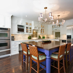 Transitional kitchen remodeling - Example of a transitional l-shaped kitchen design in Other with stainless steel appliances, stone tile backsplash, recessed-panel cabinets, white cabinets, white backsplash and wood countertops